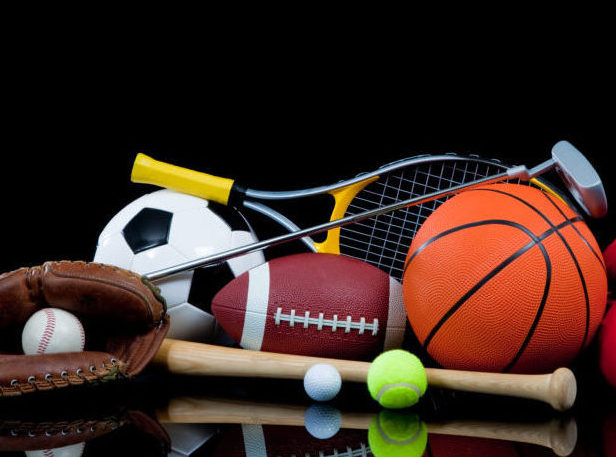 A group of sports equipment on black background including tennis, basketball, baseball, american fotball and soccer and boxing equipment on a black background