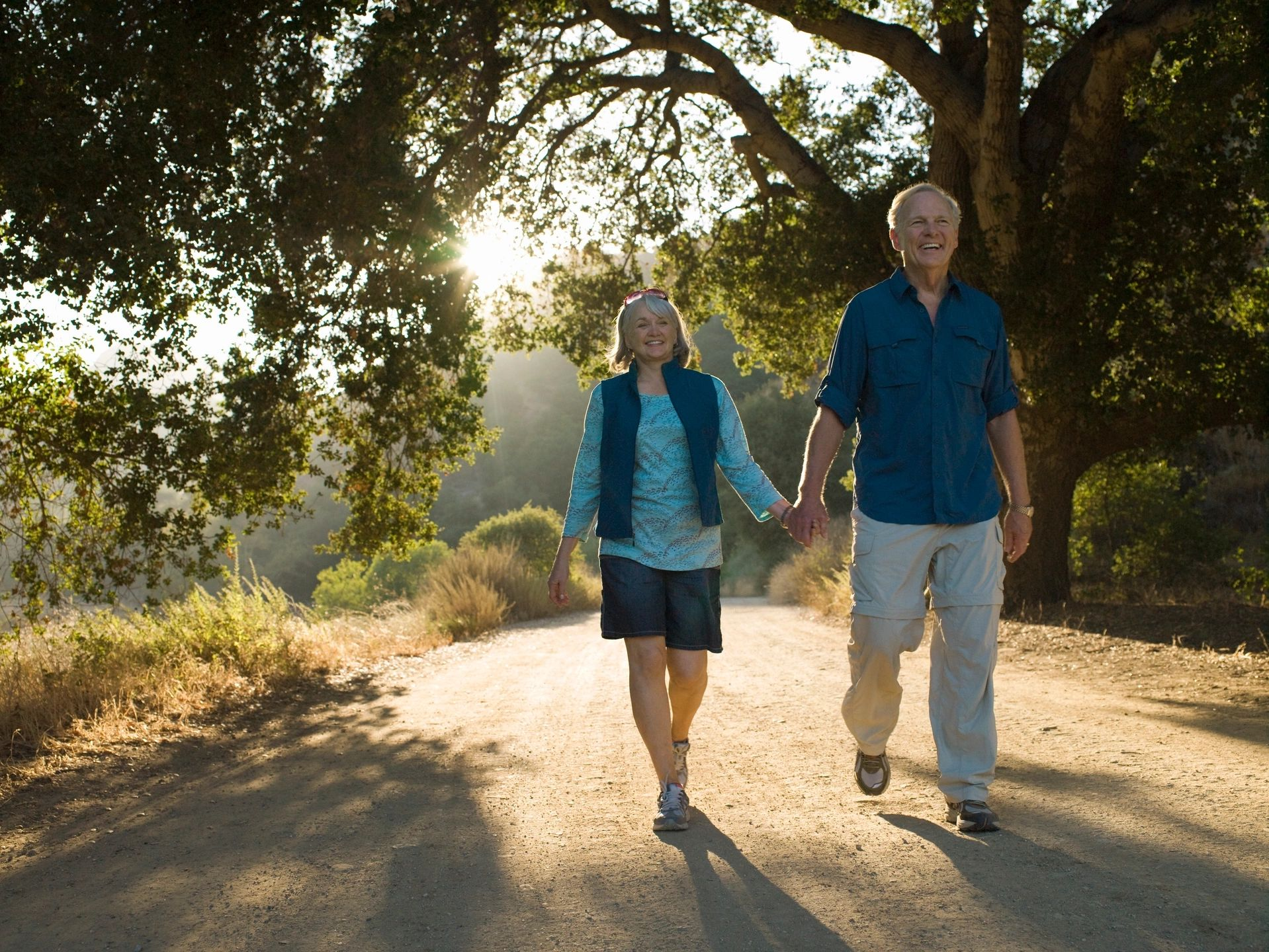 autoimmune couple walking in the woods with sunlight behind them