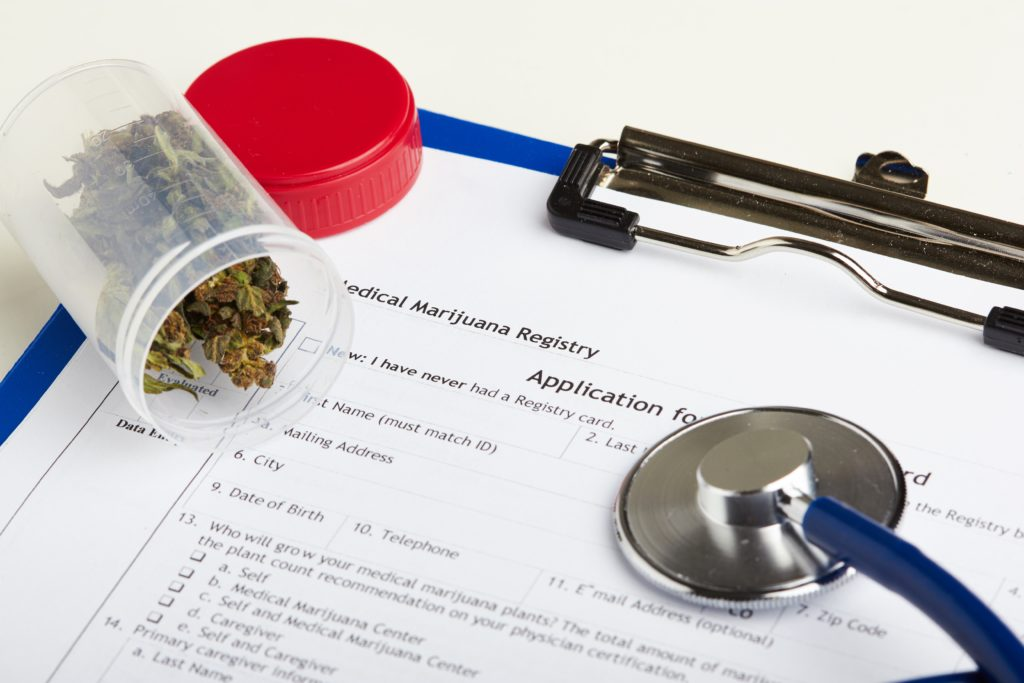 Medical marijuana in jar lying on prescription form near stethoscope. Cannabis recipe for personal use.